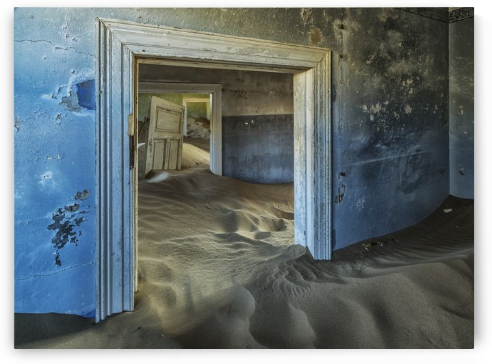 Drifting sand fills the rooms of a colourful abandoned house; Kolmanskop, Namibia by PacificStock