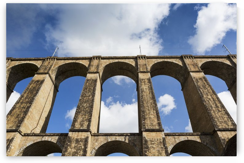 Low angle of a stone arched viaduct with blue sky and clouds; Morlaix, Brittany, France by PacificStock