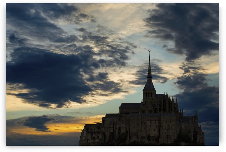 Silhouette of large stone Abbey perched on rocky hill with dramatic clouds at sunset; Mont St. Michel, Brittany, France by PacificStock