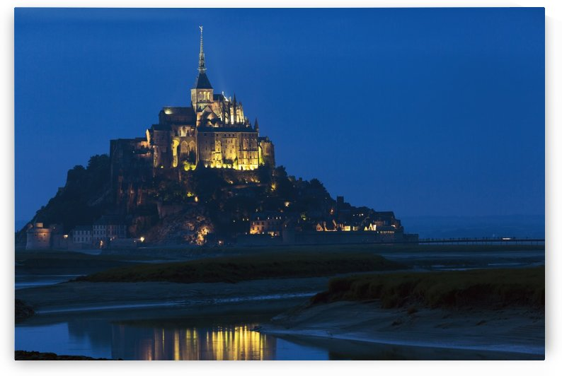 Night image of large stone Abbey perched on rocky island at low tide lit with flood lights with reflection in water; Mont St. Michel, Brittany, France by PacificStock