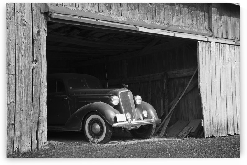 Black and white image of the front of an antique car inside a wooden barn; Frankford, Ontario, Canada by PacificStock