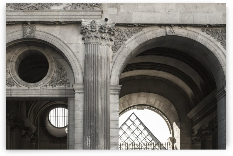Black and white image of architectural details of a passage under one of the buildings at the Louvre palace, the tip of the main pyramid is visible in the distance through the passage opening; Paris, France by PacificStock