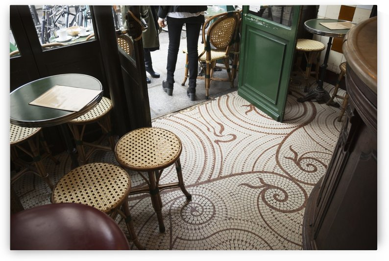 Looking down at the floor of a parisian cafe with small square tiles, traditional tables and stools, and the wooden bar; Paris, France by PacificStock