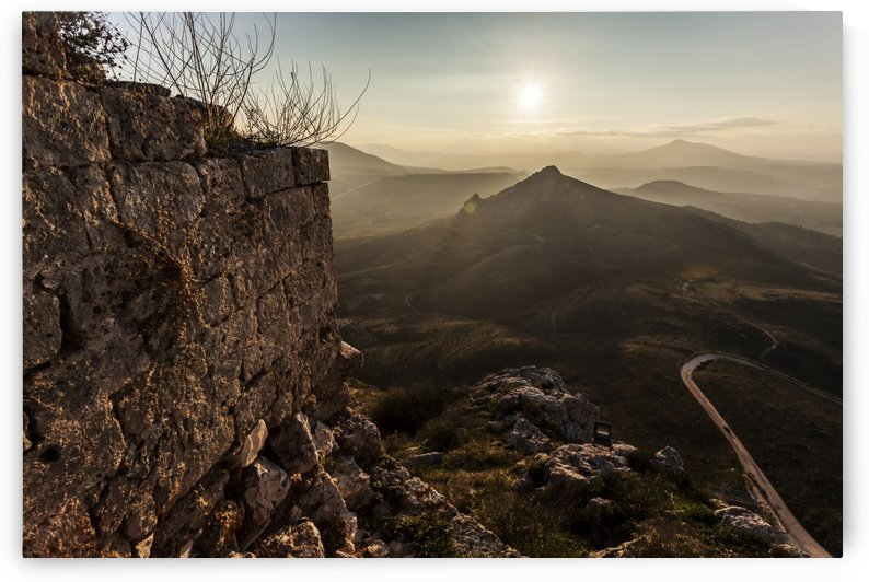Ruins of a stone wall with a sunburst and mountains; Corinth, Greece by PacificStock