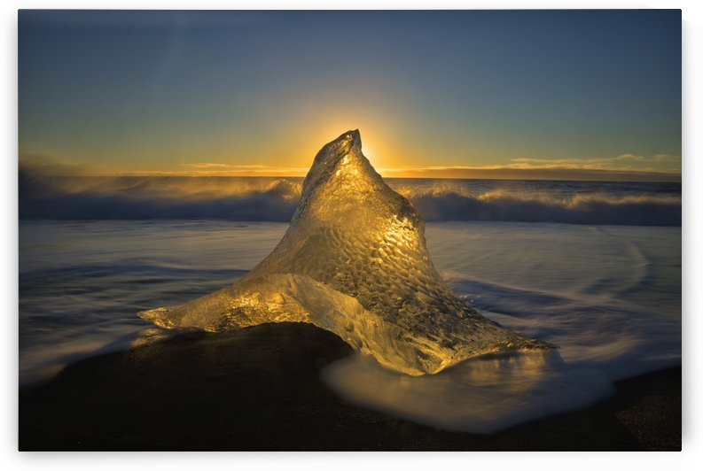 A peaked ice formation glowing golden in the sunlight; Iceland by PacificStock