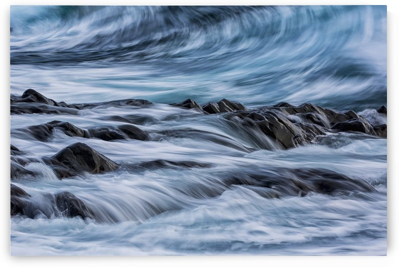 Long exposure of waves striking the coastline and flowing over rocks; Iceland by PacificStock