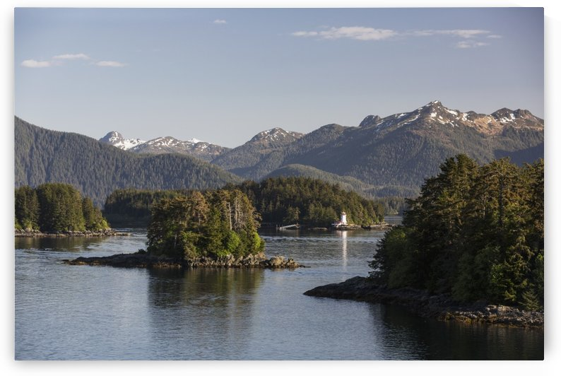 Small islands populated by Sitka spruce trees, a lighthouse in the background; Sitka, Alaska, United States of America by PacificStock