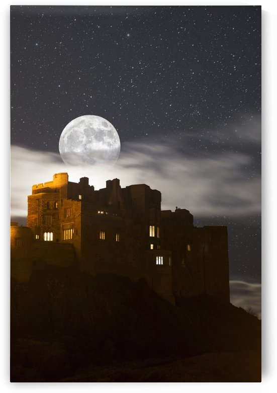 Full moon glowing in a starry sky over illuminated buildings; Bamburgh, Northumberland, England by PacificStock