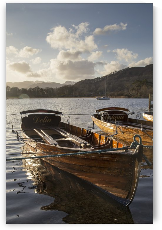 Woden boats tied at the water's edge on a tranquil lake; South Lakeland District, England by PacificStock