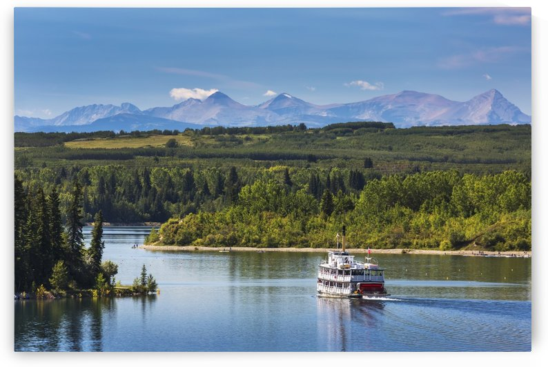 Paddlewheel boat on lake with tree lined shoreline, hills and mountains in the background and blue sky and clouds; Calgary, Alberta, Canada by PacificStock