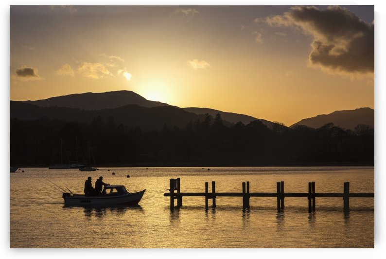 Silhouette of fishermen in a boat arriving at a dock on a lake at sunset; Keswick, Cumbria, England by PacificStock