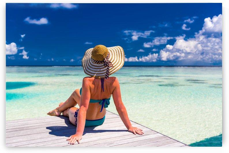 Sexy woman in bikini enjoy in tropical resort, sitting, back view by Levente Bodo