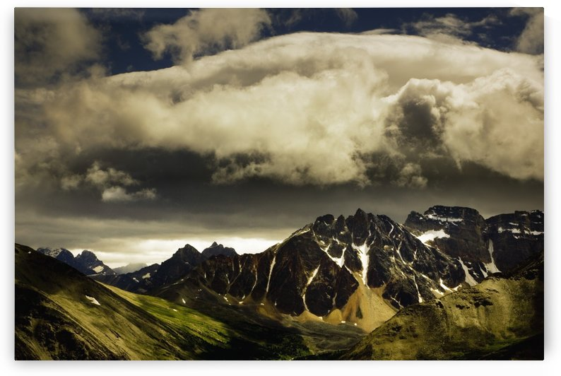 Patches Of Light Find Their Way Through Hovering Clouds Above Mountain Range by PacificStock