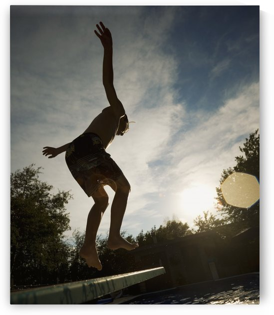 Boy Jumping Off Diving Board by PacificStock