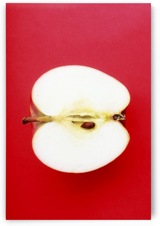 Half An Apple On Red Background by PacificStock