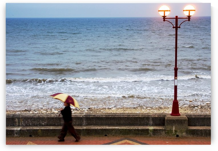 Lady With An Umbrella Walking Along Bridlington Prom, Yorkshire, England by PacificStock