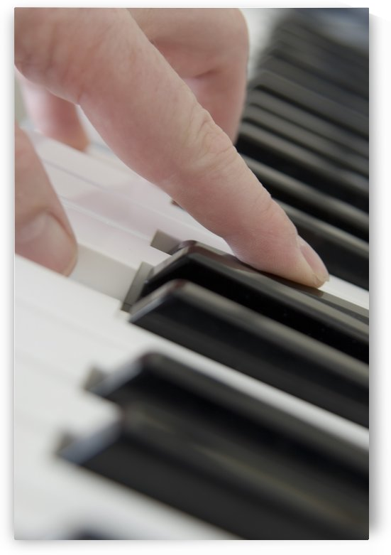 Close Up Of Finger Playing Piano Keyboard by PacificStock