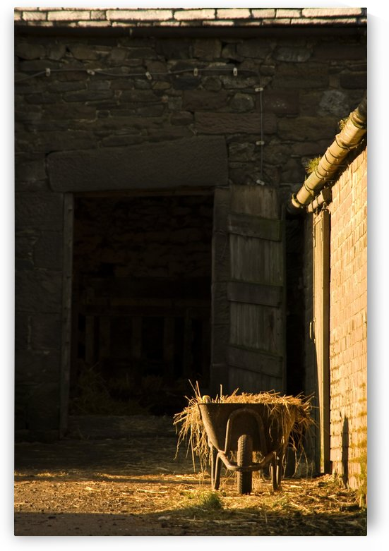 Wheelbarrow Beside A Barn by PacificStock
