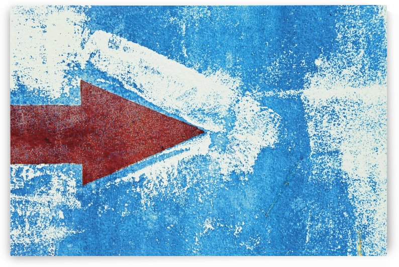 Red Arrow Painted On Blue Wall by PacificStock