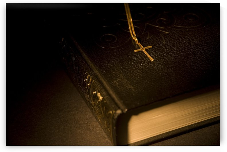 Gold Cross Pendant Resting On A Book by PacificStock
