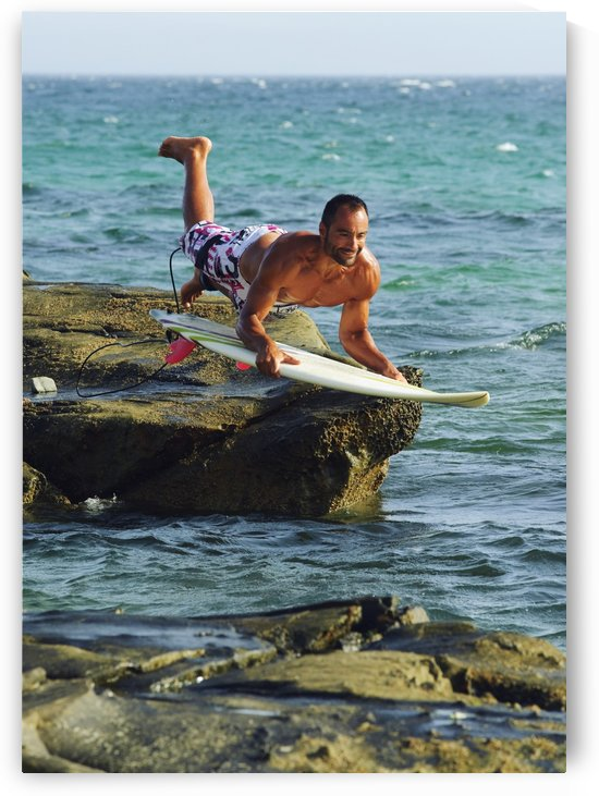 Man Jumping Into The Water On His Surf Board by PacificStock