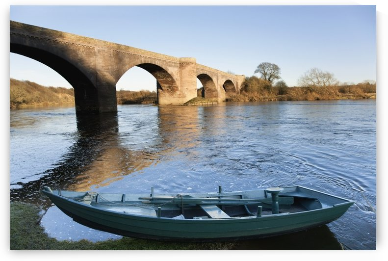 Northumberland, England; A Boat Moored On The Edge Of A River With A Bridge by PacificStock