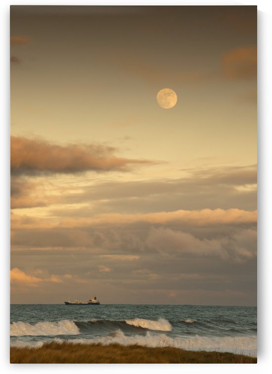 Saltburn, Teesside, England; A Cargo Ship Traveling On The Ocean With The Moon In The Sky by PacificStock