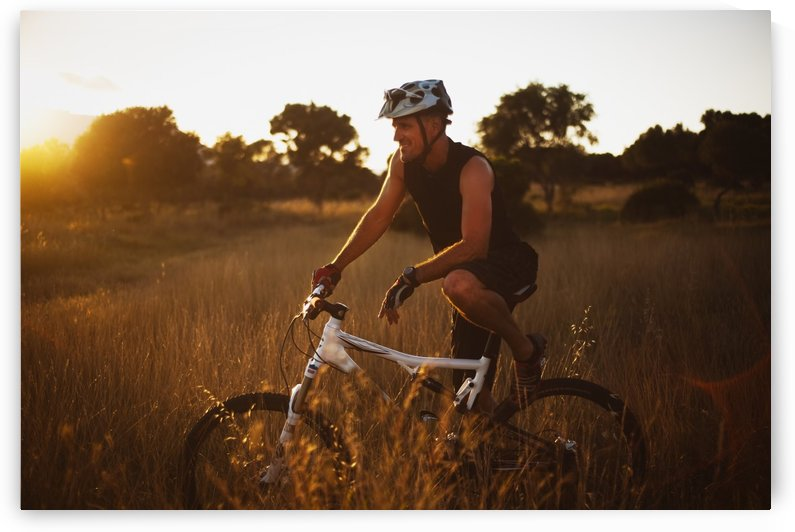 A Man Riding His Bike Through Tall Grass At Sunset In Parque Natural Los Alcornocales; Tarifa, Cadiz, Andalusia, Spain by PacificStock