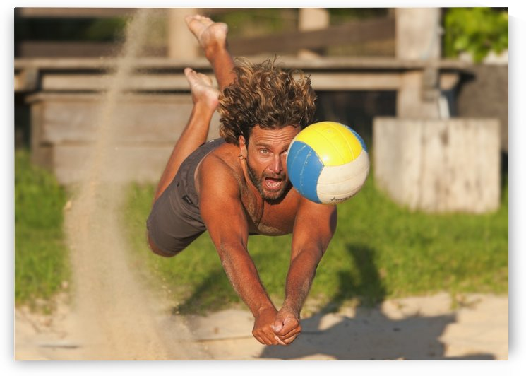 A Man Diving For A Beach Ball; Tarifa, Cadiz, Andalusia, Spain by PacificStock