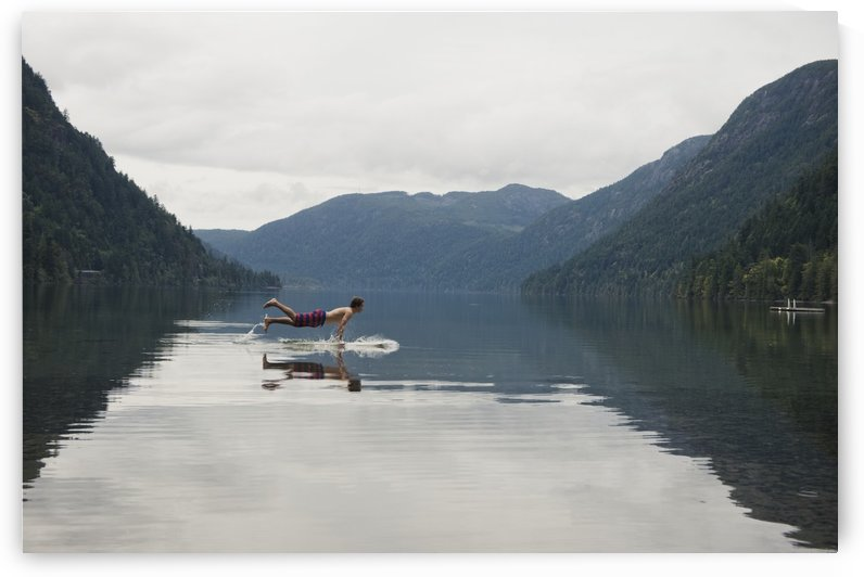 A Young Man Leaps Onto His Body Board In Cameron Lake; British Columbia Canada by PacificStock