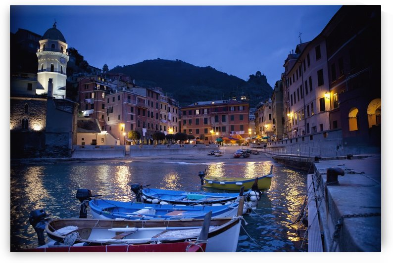 Boats Moored By Buildings Along The Waterfront At Night; Vernazza, Liguria, Italy by PacificStock