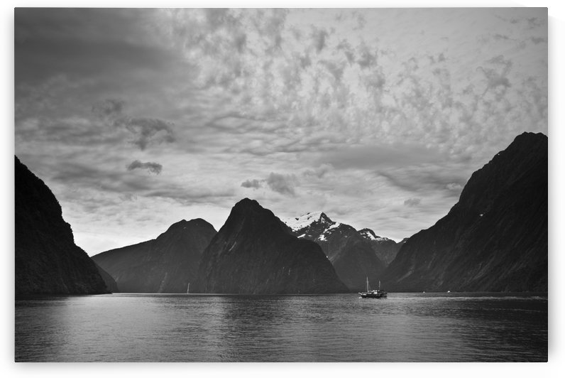A Boat In The Water Along The Coast Surrounded By Mountains; Milford Sound, South Island, New Zealand by PacificStock