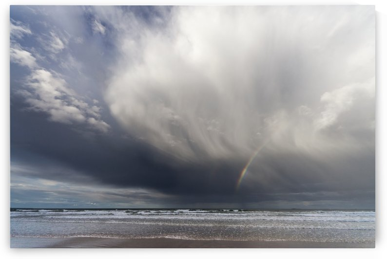 A Rainbow In The Dark Clouds Over The Ocean; Bamburgh, England by PacificStock