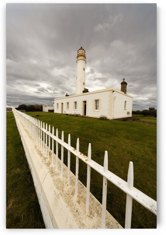 A White Fence Beside Barns Ness Lighthouse; Lothian, Scotland by PacificStock