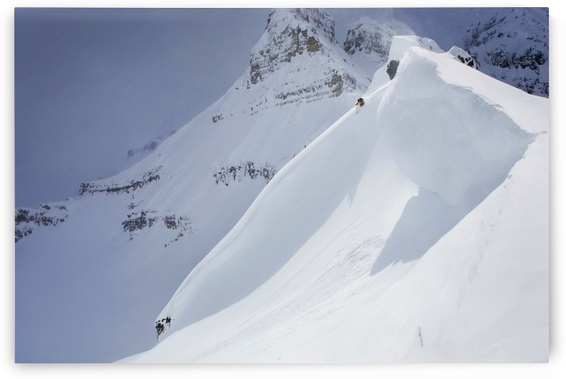 Skier On Crest Of Big Drop, Dwarfed By Mountain; Canada, British Columbia, Icefall Lodge by PacificStock