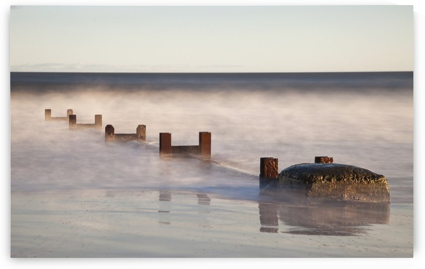 Wooden Posts And Boulders Immersed In Water At The Coast; Northumberland, England by PacificStock