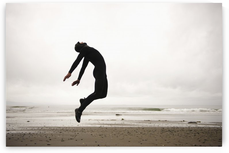 An Individual Wearing A Wet Suit Jumping In Mid-Air On A Beach; French Beach, British Columbia, Canada by PacificStock