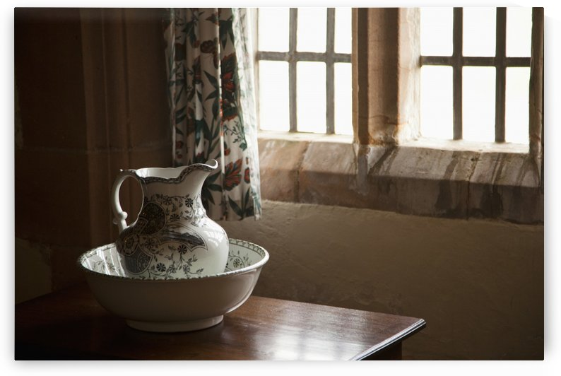 A Pitcher And Basin Sit On The Table Beside A Window; Lindisfarne, Northumberland, England by PacificStock