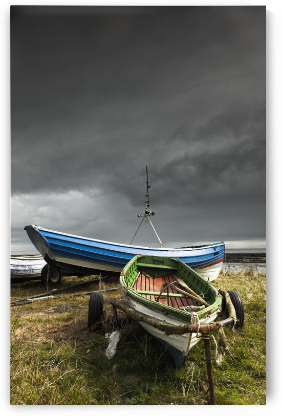 Rowboats sitting on trailers on the shore under storm clouds;Boulmer northumberland england by PacificStock