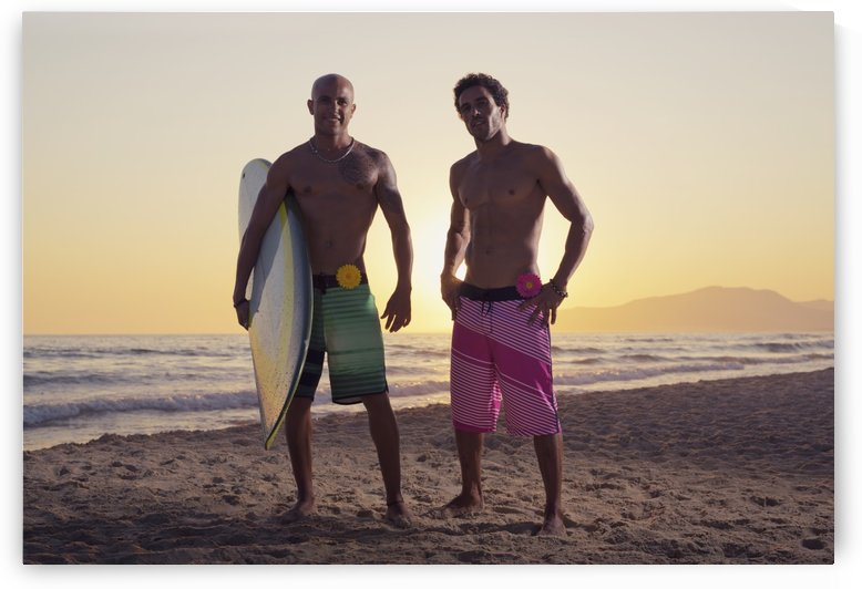 Two young men standing on the beach with a surfboard;Tarifa cadiz andalusia spain by PacificStock