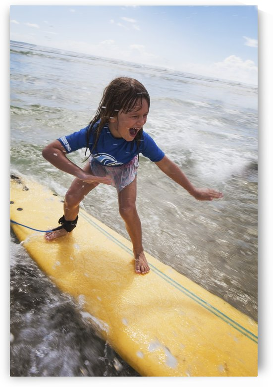A young girl on a yellow surfboard;Gold coast queensland australia by PacificStock