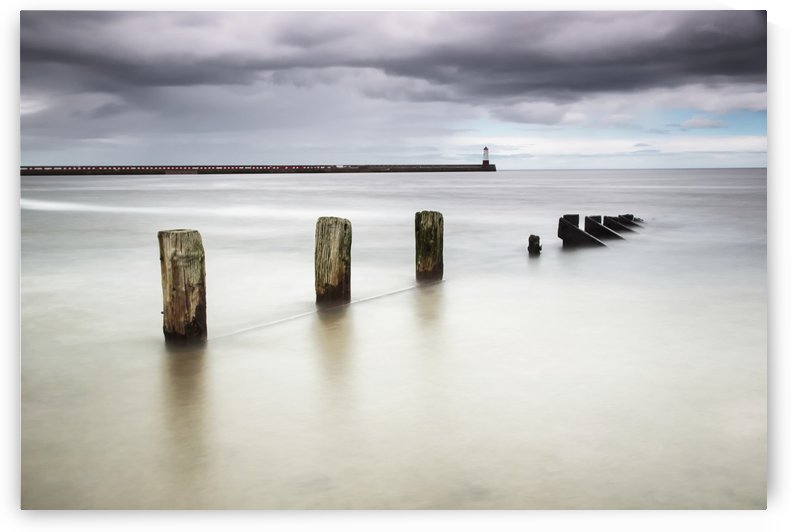 Wooden posts in the ocean with a lighthouse at the end of a pier by PacificStock