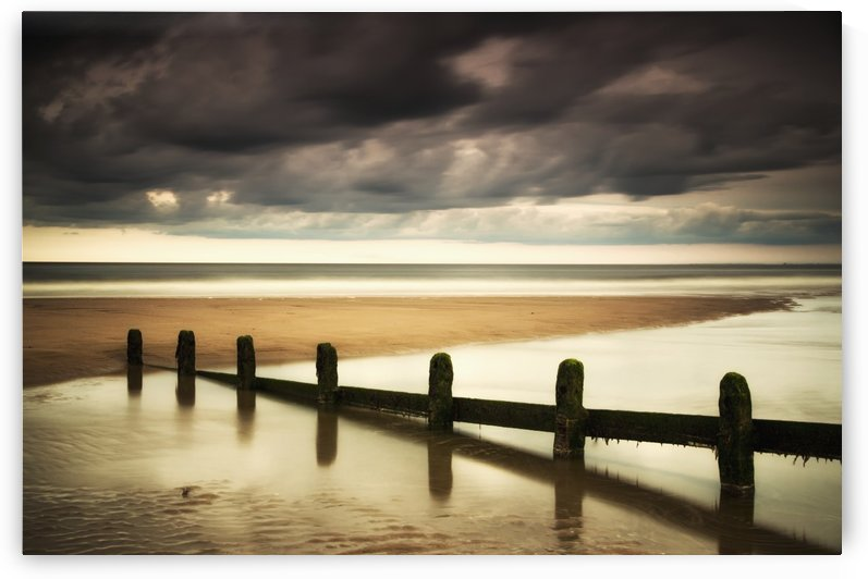 A fence submerged in the water at the coast with storm clouds overhead;Berwick northumberland england by PacificStock