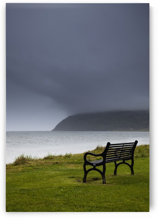 A bench at the water's edge with a dark stormy sky;Moray firth scotland by PacificStock