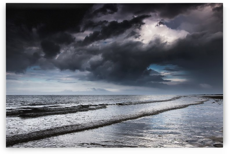 Dark storm clouds over the ocean with waves rolling into the shore;Druridge bay northumberland england by PacificStock