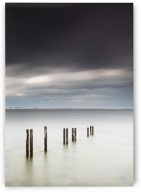 Wooden posts in a row in the shallow water along the coast with a view of a city in the distance under dark storm clouds;St. mary's bay northumberland england by PacificStock