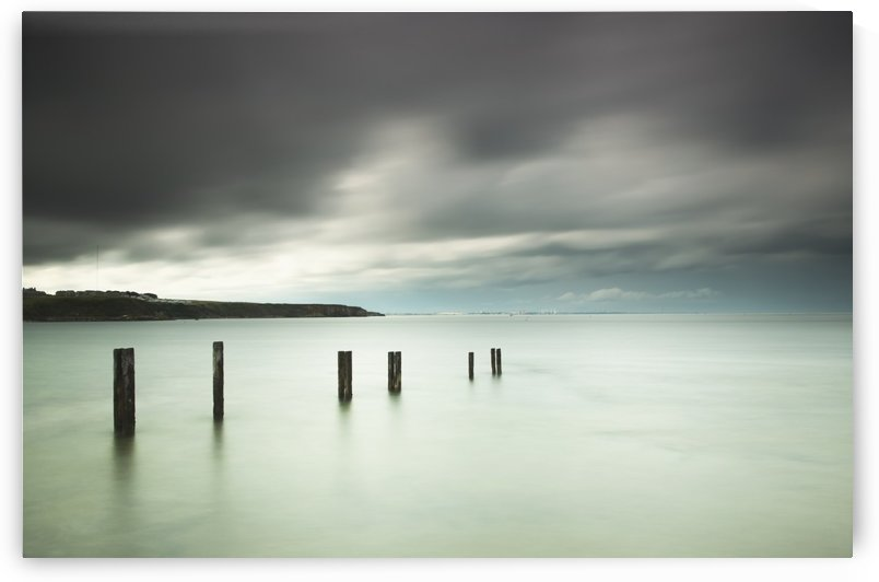 Wooden posts in a row in the shallow water along the coast under storm clouds;St. mary's bay northumberland england by PacificStock