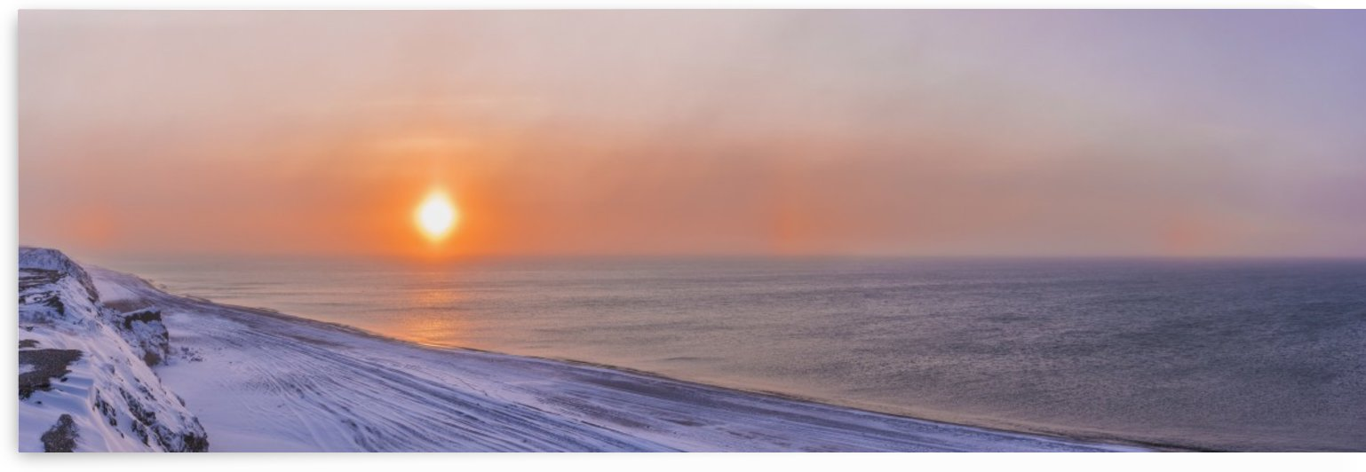 Sunset through windblown snow creates a sundog above the Beaufort Sea along the coast just outside of Barrow, Winter, Arctic Alaska, USA. by PacificStock