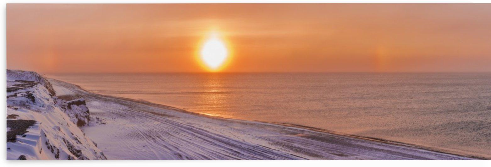Sunset through windblown snow creates a sundog above the Beaufort Sea along the coast just outside of Barrow, Winter, Arctic Alaska, USA. by PacificStock