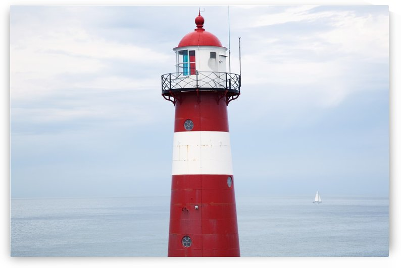 Red and white lighthouse along the coast with a sailboat in the distance near westkapelle;Zealand, netherlands by PacificStock